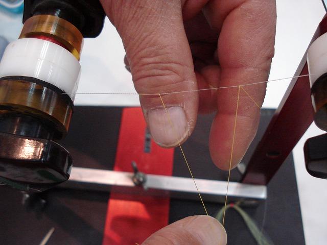 左手の輪を親指と人差し指で広げて持ち、その輪の中に2本の糸を入れる。